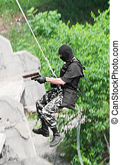 Armed soldier rappelling with a gun