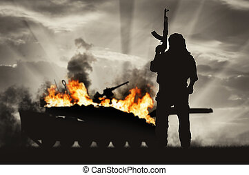 Armed terrorist and burning tank