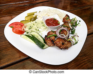 Armenian dish shashlik from pork or lamb meat served with rice, onions, vegetables and sauce