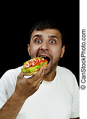 Armenian man eating hotdog