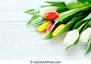 armful of flowers on a wooden background