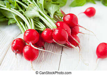 armful of fresh red radish on the boards