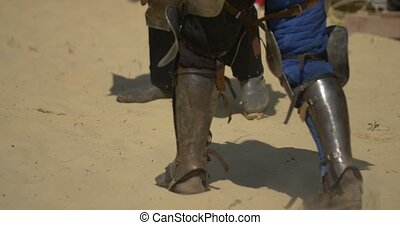 Armored feets of the warriors that is fighting on the sand...