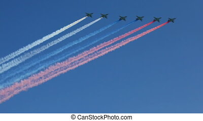 MOSCOW - MAY 9: armored subsonic attack planes Su-25 fly in sky leaving trail of smoke as tricolor Russian flag on parade in honor of Great Patriotic War victory on May 9, 2010 in Moscow, Russia.