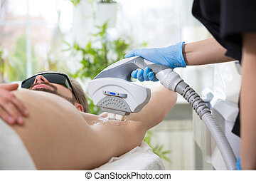 Armpit laser epilation at beautician's - Men lying at...