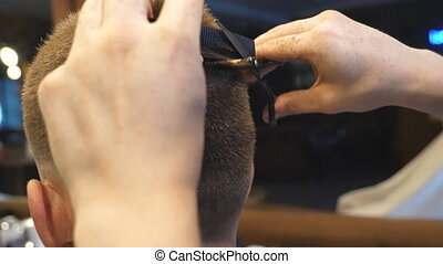 Arms of barber trimming hair of client in barbershop. Male...