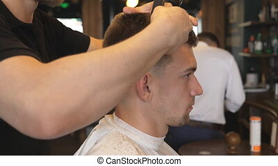 Arms of barber trimming hair of client in salon. Male hands...