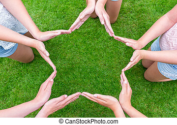 Arms of girls with hands making star shape above grass -...