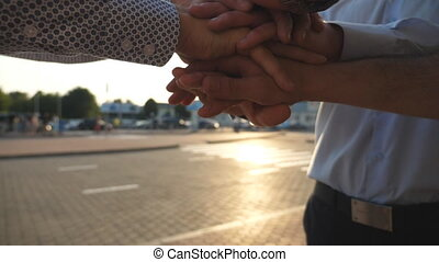 Arms of three business men stacked together in unity and teamwork. Hands of businessman team getting together in the center of a circle and then raised. Sun flare at background. Slow motion Close up