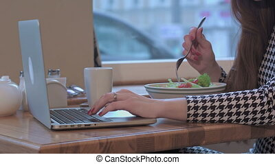 Arms of young businesswoman using a laptop for work. She is sitting at the table in cafe and eating a salad