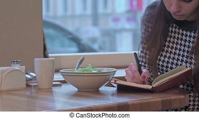 Arms of young businesswoman writing in note book. She is sitting at the table in cafe and eating a salad
