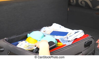 Arms of young woman open a suitcase and unpack personal...