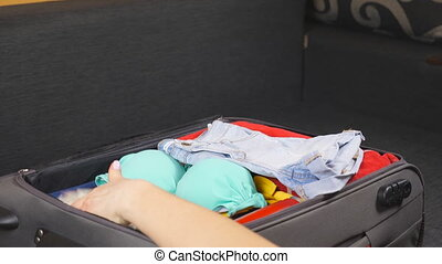 Arms of young woman packing bag with personal stuff for trip or vacation. Girl gets ready for flight to resort. Female hands putting summer things in a suitcase. Concept of travel. Side view Close up