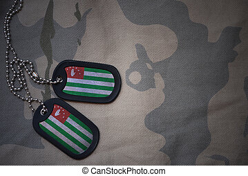 army blank, dog tag with flag of abkhazia on the khaki texture background. military concept