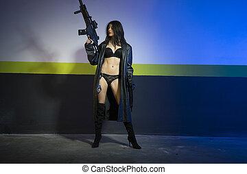 Army brunette girl with gun in a garage in attitude shoot, dressed in bulletproof vest