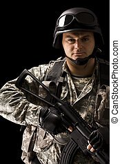 army forces - soldier holding a gun, isolated in black