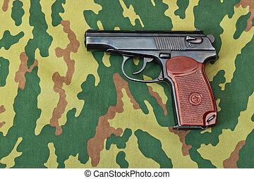 Army handgun on camouflaged background