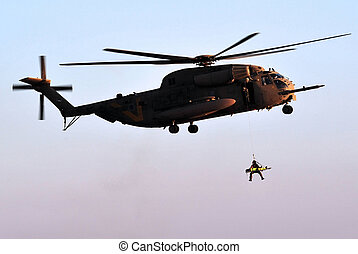 An Israeli military helicopter CH-53 Sikorsky picks up a soldier after rescuing an injured soldier from the field.