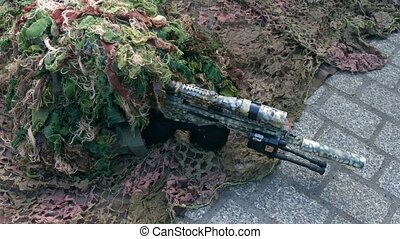 Army sniper wearing disguise camouflage suit at military show. 4K clip
