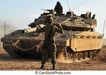 Army soldier in a field with his tank and weapons