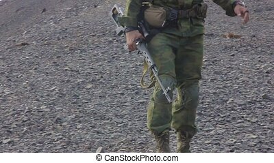 Army soldier with Sniper rifle in action in mountains. goes...