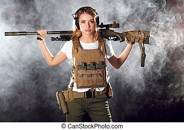 Army woman with gun over smoky darkness