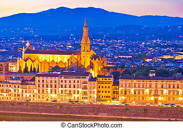 Arno river waterfront and illuminated church in Florence evening view