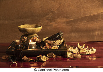 Aroma lamp with essential oil and potpourri on wooden table background.