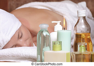 Woman on massage table with oils, essential oils, candles, scents. Focus on products.
