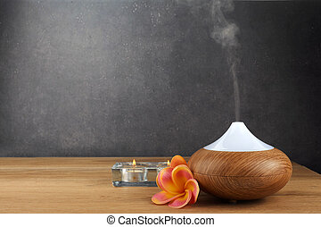 Aroma oil diffuser, candles and flowers on wooden table
