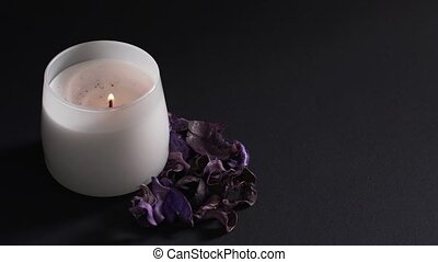 Aromatherapy concept - a woman's hand sets fire to a white candle isolated on a black background. Dry fragrant flowers for relaxation and meditation in the spa 4k