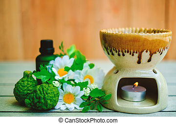 Aromatherapy essential oil burner on the wooden table with bergamot and flower