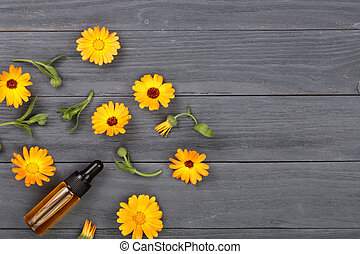 aromatherapy essential oil with marigold flowers on black background with copy space for your text. Top view