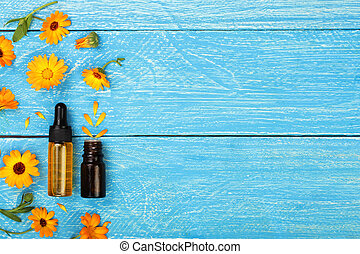 aromatherapy essential oil with marigold flowers on blue background with copy space for your text. Top view