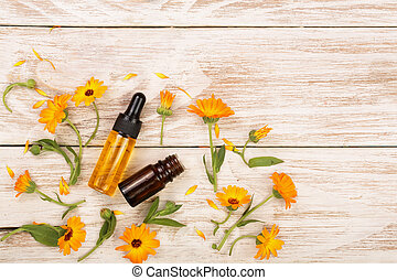 aromatherapy essential oil with marigold flowers on white background with copy space for your text. Top view