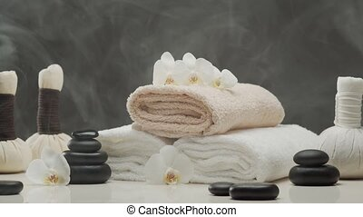 Aromatherapy, oriental massage and spa treatment concept. Relaxation composition of towels, candles, flowers, stones and herbal balls.