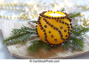 Aromatic Christmas orange with cloves and candle