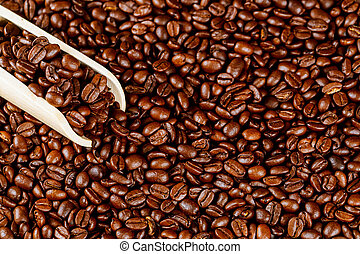 Aromatic coffee beans with wooden spoon. Close up.