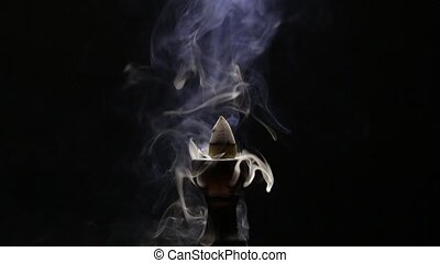 Aromatic cone smoldering in a ceramic stand and emits smoke...