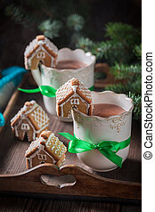 Aromatic gingerbread cottages with sweet drink as Christmas snack