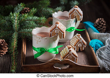 Aromatic gingerbread cottages with sweet drink for Christmas