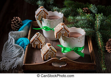 Aromatic gingerbread cottages with sweet drink in Christmas evening