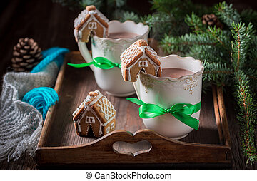 Aromatic gingerbread cottages with sweet drink in Christmas winter evening