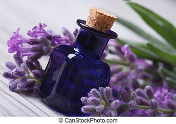 aromatic lavender oil and beautiful flowers on the wooden -...
