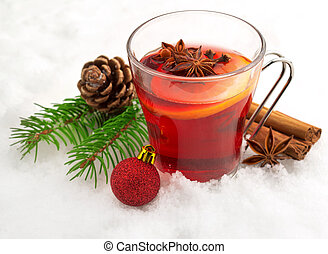 aromatic mulled wine - mug of mulled wine and spices in snow