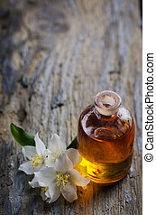 Aromatherapy concept. Massage oil and jasmin flower on rustic wooden table.