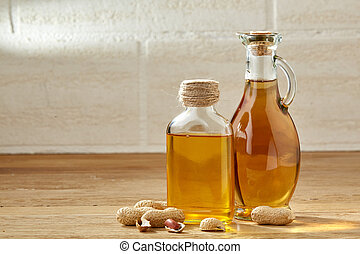 Aromatic oil in a glass jar and bottle with peanuts on wooden table, close-up.