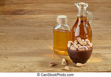 Aromatic oil in a glass jar and bottle with pistachios in bowl on wooden table, close-up.