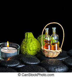 Aromatic spa concept of bergamot fruits, candle and bottles esse