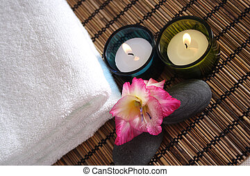 orchid, candle pebbles and white towel on bamboo mat for spa